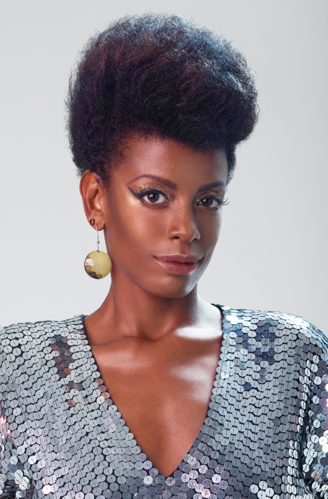 A atriz e cantora Thalma De Freitas com um afro no estilo 80s, o flat top