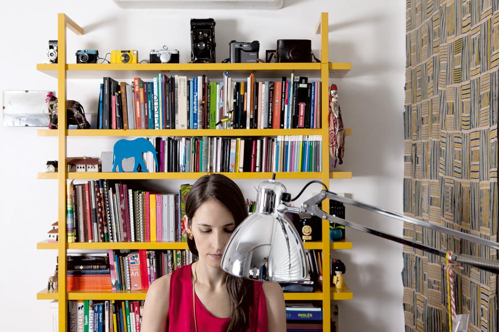 Cabe tudo - A estante amarela foi desenhada pelas arquitetas e abriga os livros e a coleção de câmeras fotográficas de Mariana. À direita, tecido africano