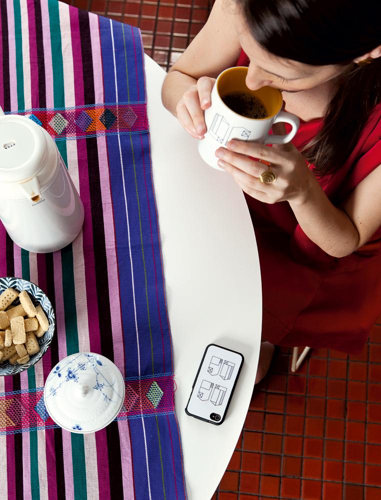 Customizada - Mariana toma café em xícara personalizada com um desenho seu. A capa do iPhone também tem desenho de sua autoria