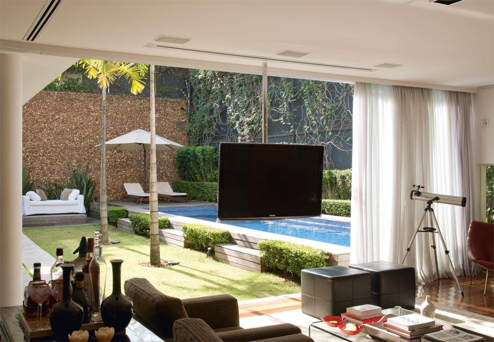 Integrada  As enormes portas de vidro garantem uma integração total da sala com o jardim. A casa foi toda automatizada pela TAAG, e o suporte da TV de LCD possibilita que ela seja assistida de dentro da sala ou do jardim. As poltronas e o pufe de couro foram desenhados por Vanessa