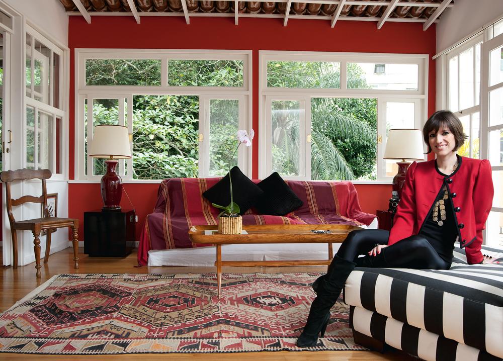 Antiguinho - Na sala, toda envidraçada, Constança faz pose na sua poltrona favorita, que possui há mais de 15 anos. O tecido listrado foi comprado em uma loja no centro do Rio. O tapete Kilin foi presente do pai. O tecido que forra o sofá foi comprado em um antiquário do shopping de antiguidades da rua Siqueira Campos