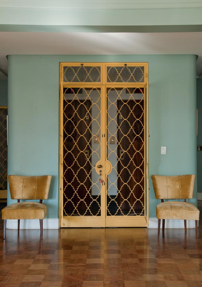 Original - A porta de ferro, pintada de amarelo, está no apartamento desde o primeiro morador. A madeira do piso original era mais avermelhada e foi clareada. As poltronas anos 50 compradas na feira da praça Benedito Calixto