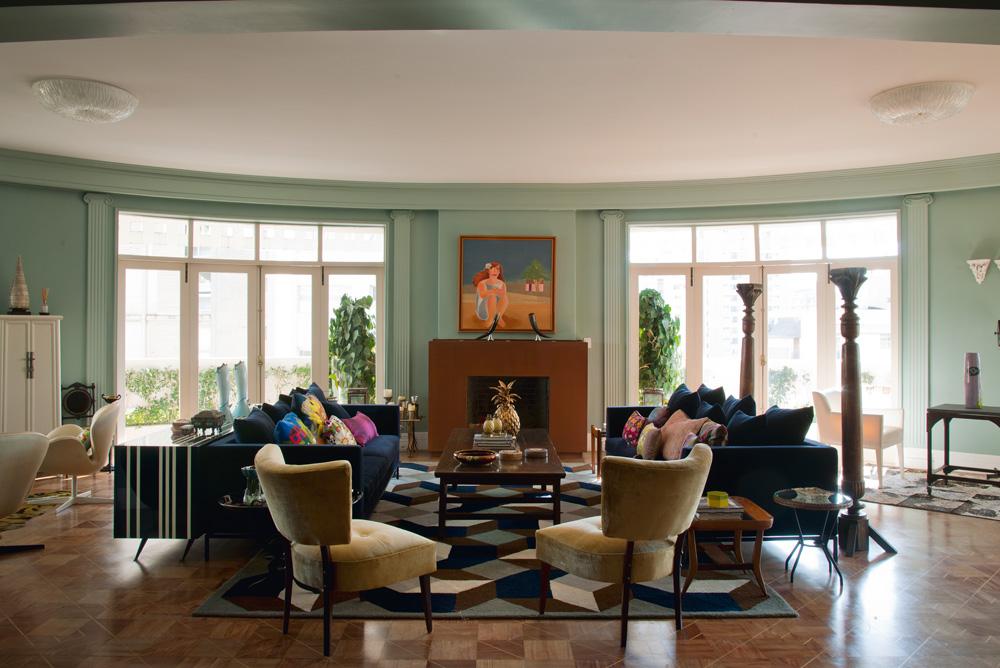 Sem canto - Quando entram no apartamento, os visitantes dão de cara com a enorme sala de estar redonda. Os sofás azul-marinho são da Micasa e o tapete foi desenhado por André Lima para a Firmacasa. A mesa de centro, da L'oeil, faz par com as duas colunas de madeira da Secrets de Famille