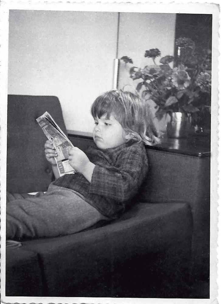 No sofá de casa, fingindo ler um gibi, aos 3