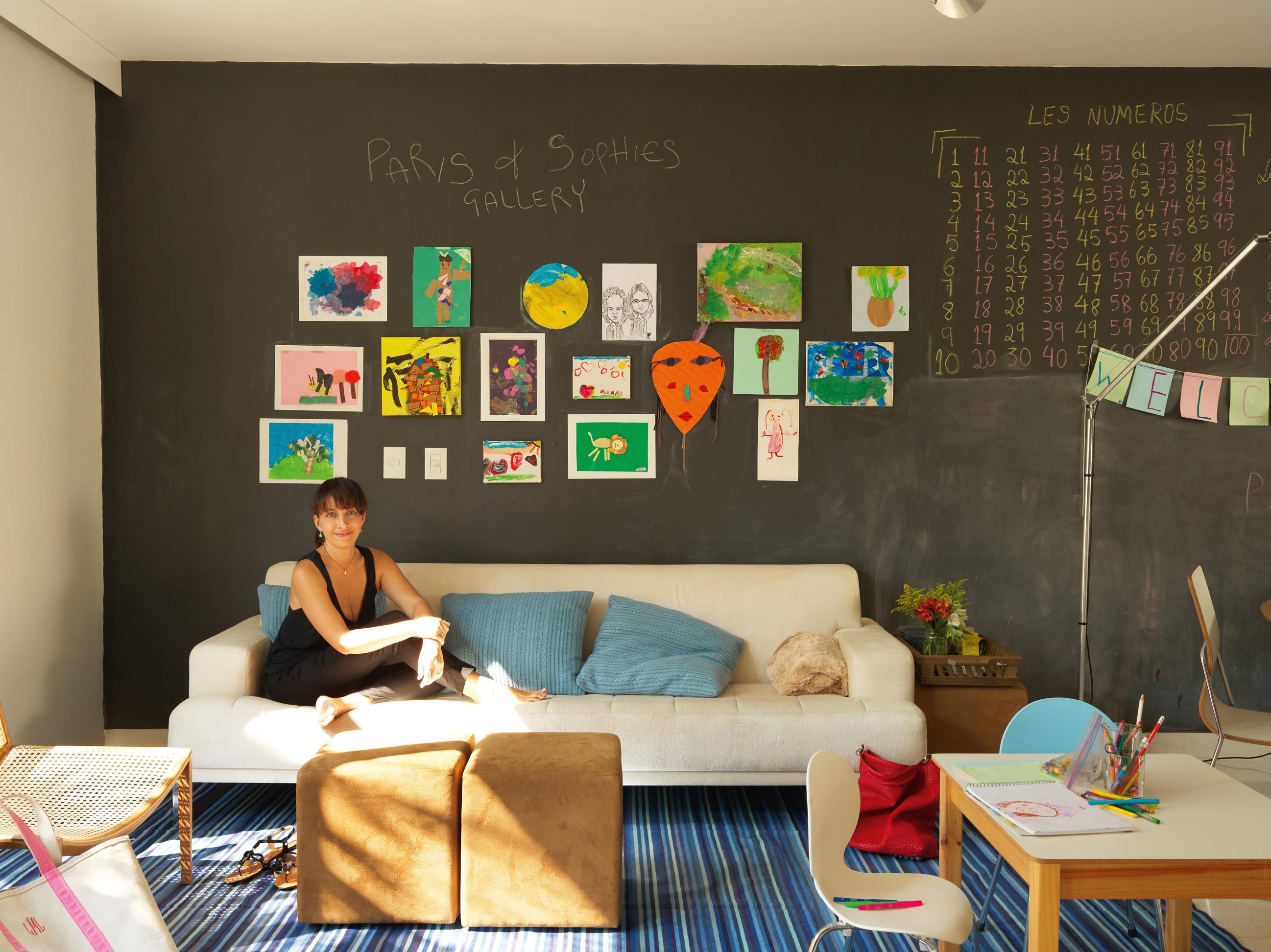 Multifuncional - Lina na garagem que virou family room. A parede de trás ganhou cinco mãos de esmalte fosco preto para dar o efeito de lousa escolar. Sofá da Artefacto, mesa e cadeiras da Hits Kids'n'Teens. Tapete dhurrie de algodão indiano Square Foot
