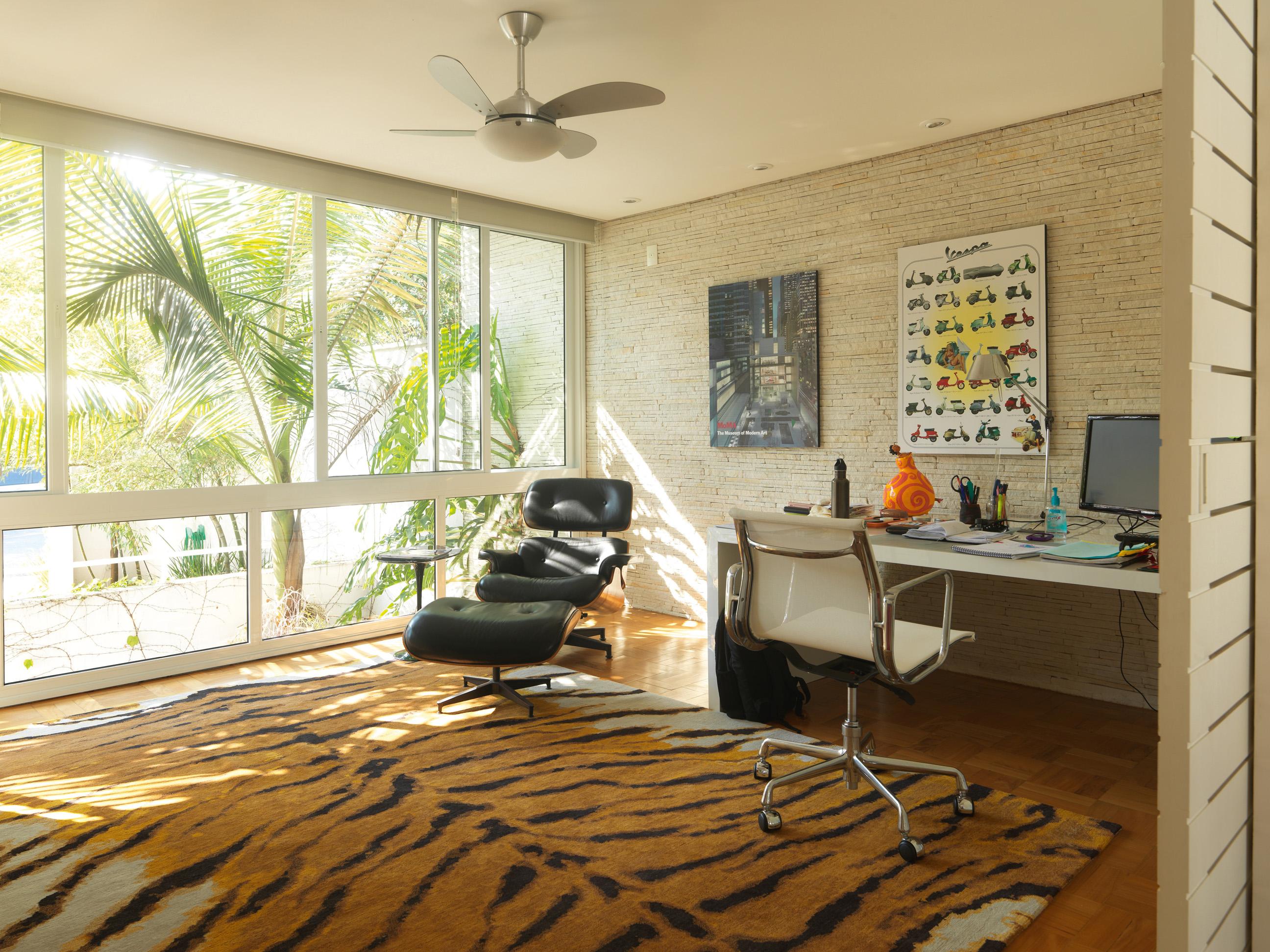 Tropical - Escritório de Lina, onde era o showroom de sua empresa até pouco tempo atrás. O tapete com estampa de tigre, de lã tibetana, é da coleção de Lina. A poltrona e a cadeira são de Charles Eames e a mesa foi feita por marceneiro
