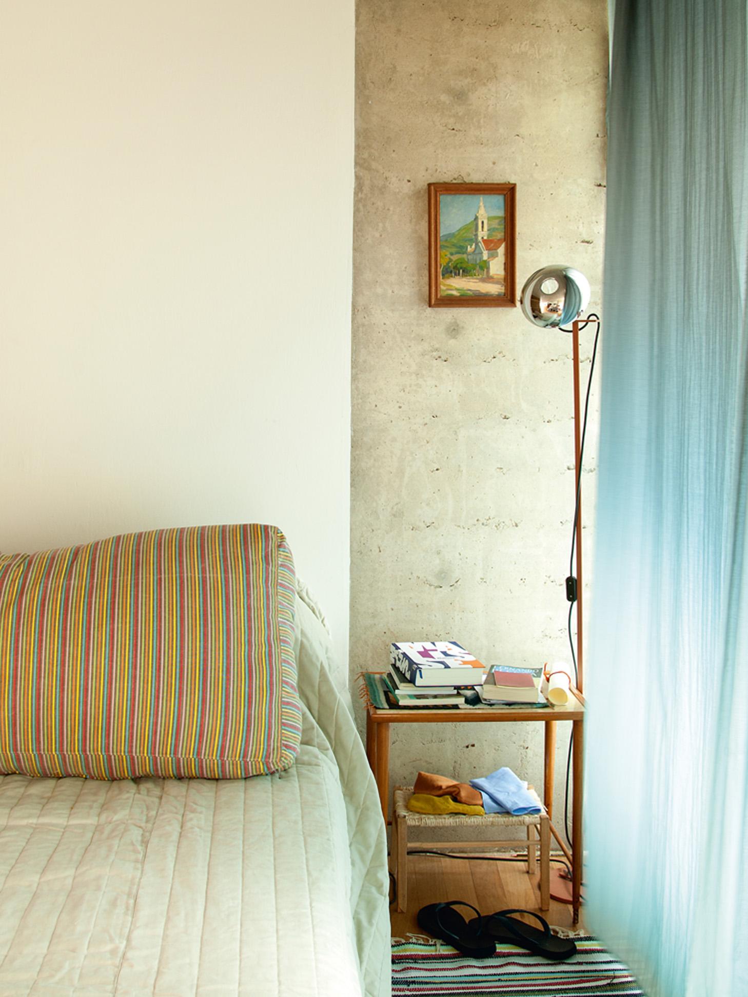 Traços simples - O criado-mudo, que Lucia não lembra onde comprou, guarda os livros preferidos do mês. Acima dele, (mais) um quadro de Angelo Guido
