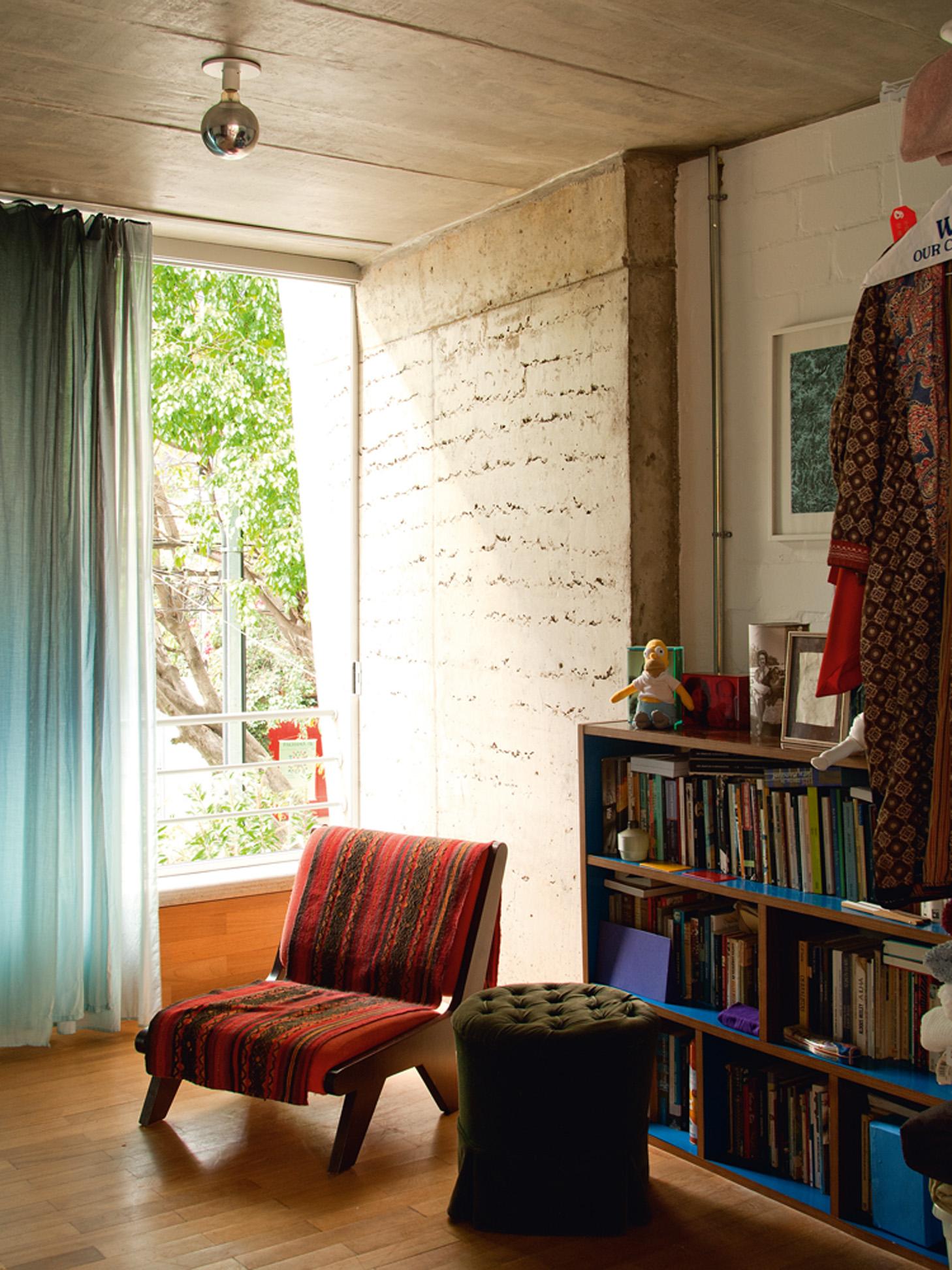 Aconchego - O outro canto do quarto do casal, que guarda a estante com os livros e a poltrona, também forrada com tecido que a protege das gatas Mulata e Elza