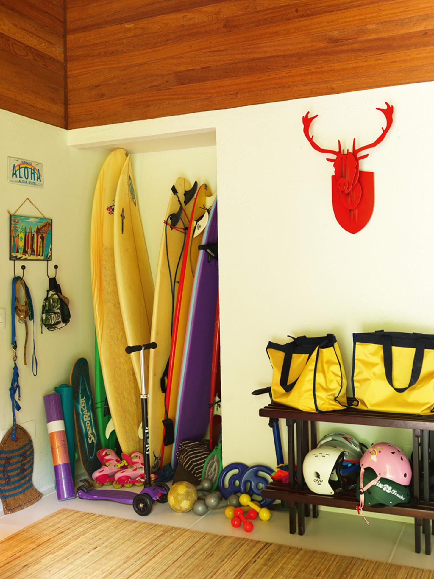 """Da praia: O hall de entrada da casa serve tanto de área de acesso aos quartos como de """"estacionamento"""" das pranchas do marido, Felipe, e guarda-tralhas das crianças"""
