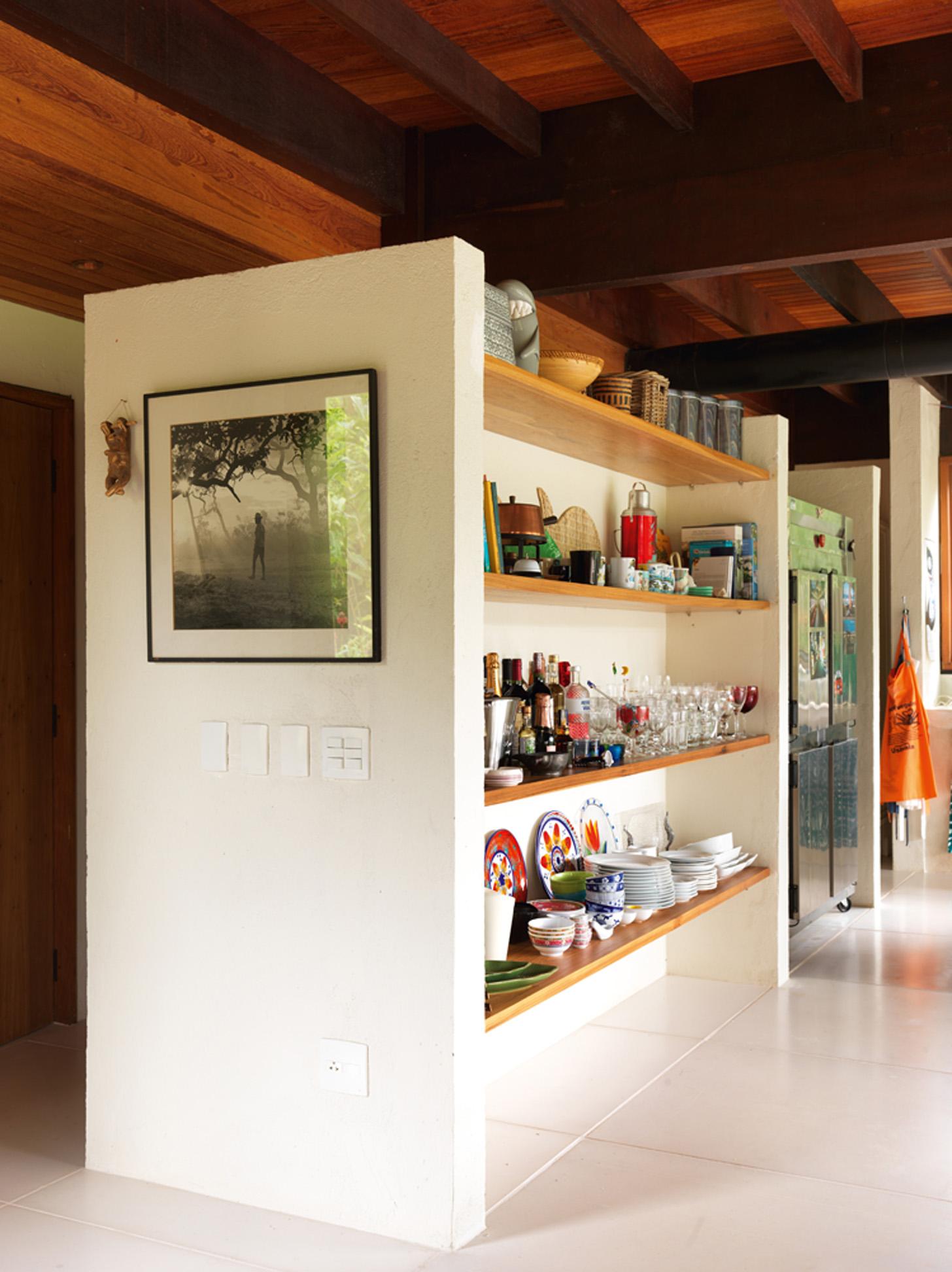 À mão: Na cozinha, as estantes de madeira fazem as vezes de armários e deixam os objetos à mostra, fáceis de pegar. Fotografia de Marcos Prado, amigo da família