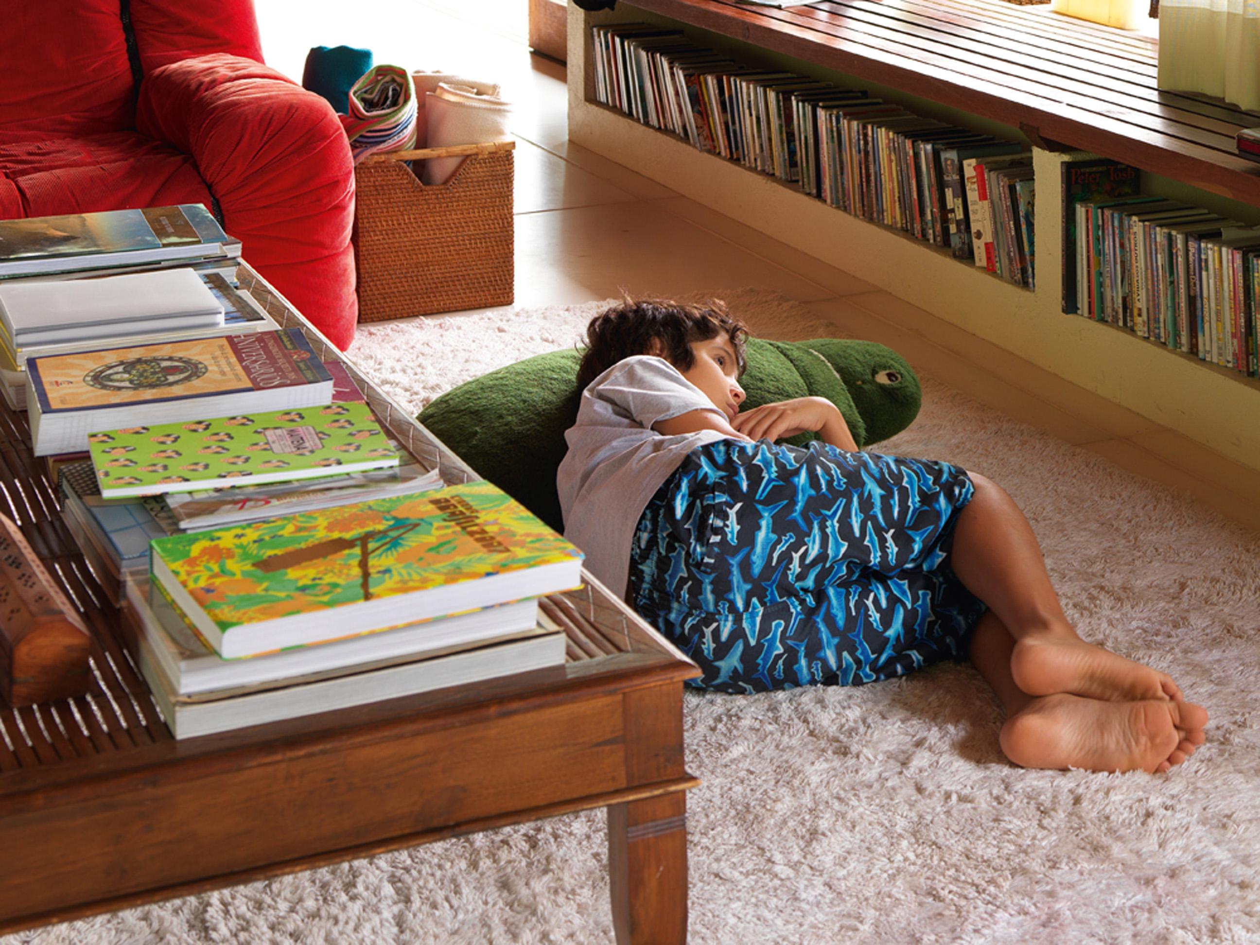 Lazer: Antônio descansa vendo TV deitado em sua tartaruga gigante de pelúcia. A bancada de alvenaria com tampo de madeira foi desenhada pelo arquiteto e acomoda a coleção de DVDs. A mesa de centro é de Bali
