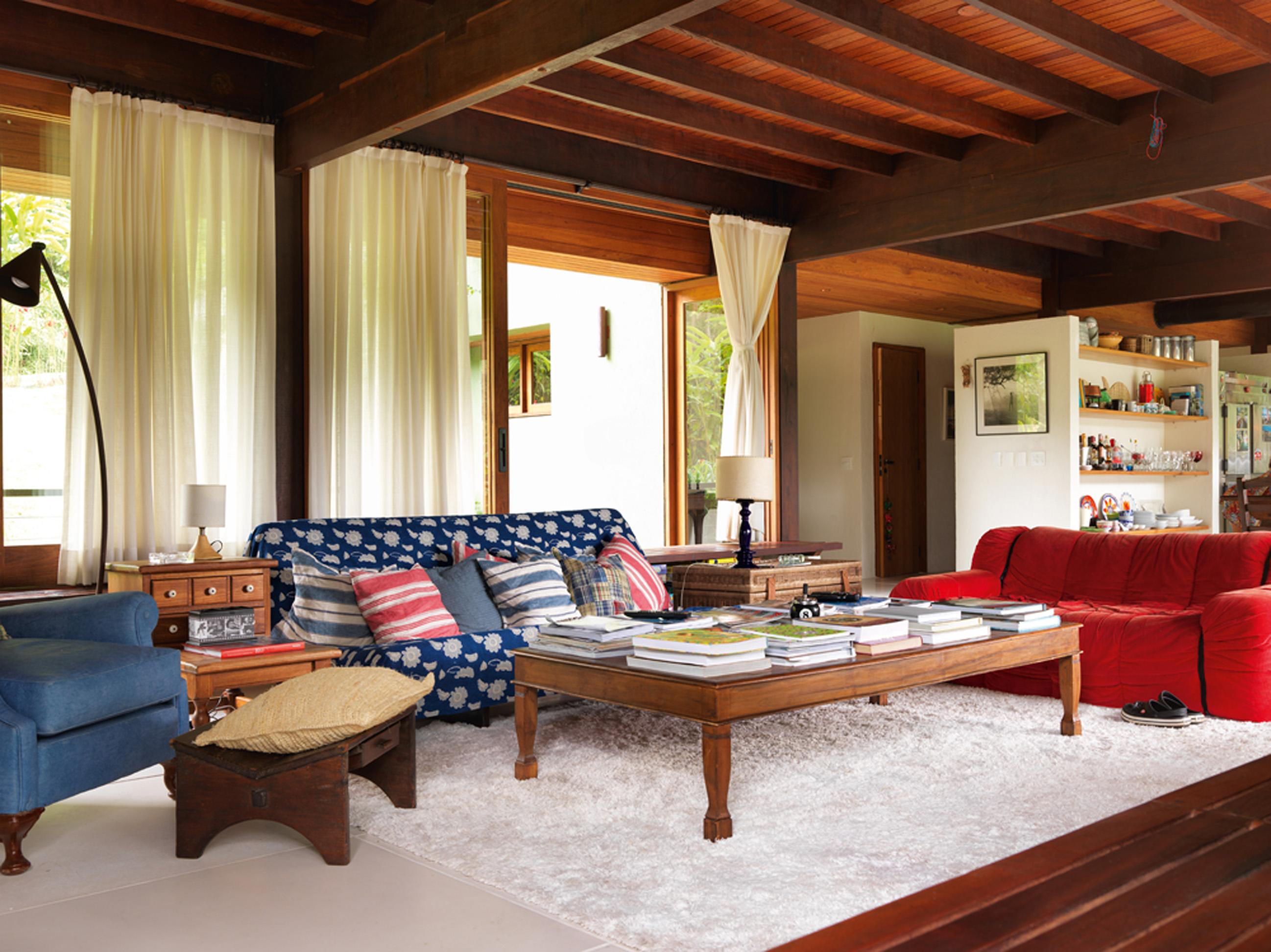 Senta lá: Outra perspectiva da ampla sala. O sofá vermelho é da Forma e o sofá coberto com o tecido é da Futon Company