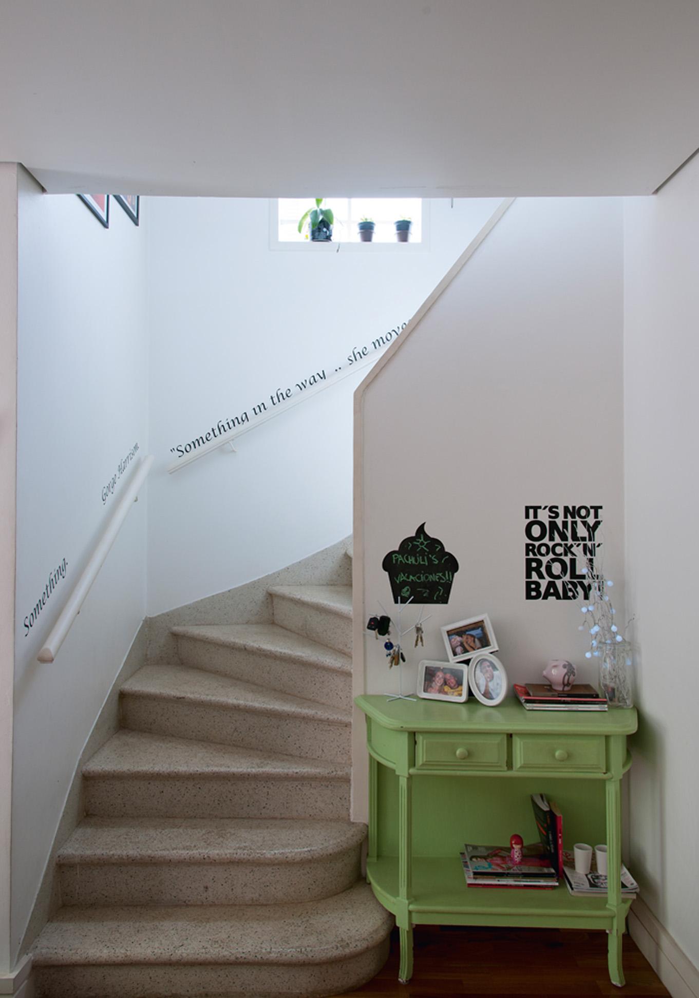 """Escada musical: Nas paredes da escada, adesivo com a letra da música """"Something"""" de George Harrisson, feito na Grudado. O móvel verde era da mãe de Ana"""