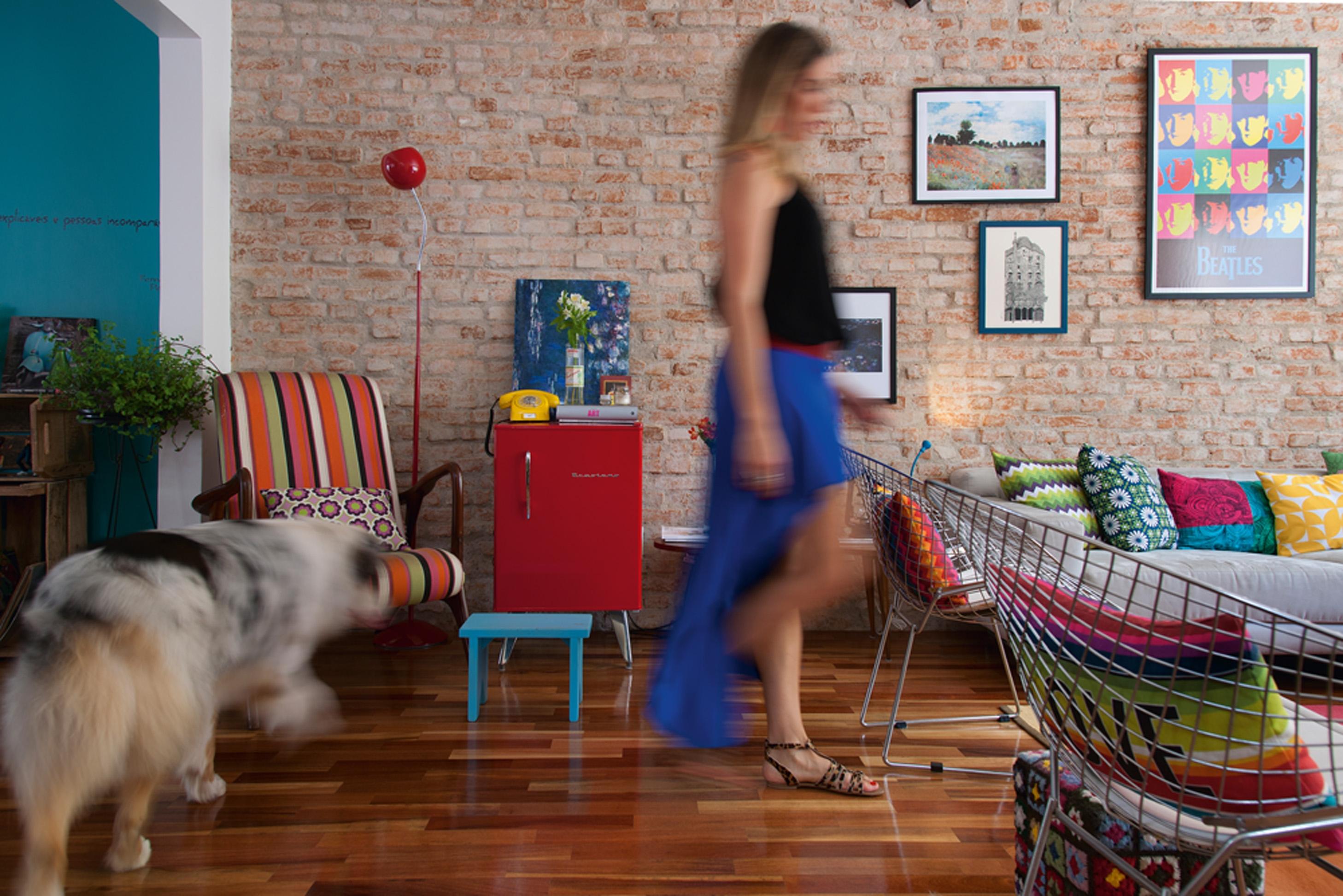 Restauração: O piso era cerâmico e foi substituído por tacos de Ipê. Poltrona listrada Desmobília, sofá e banquinho azul da Tok&Stok e poltronas de arame Etna