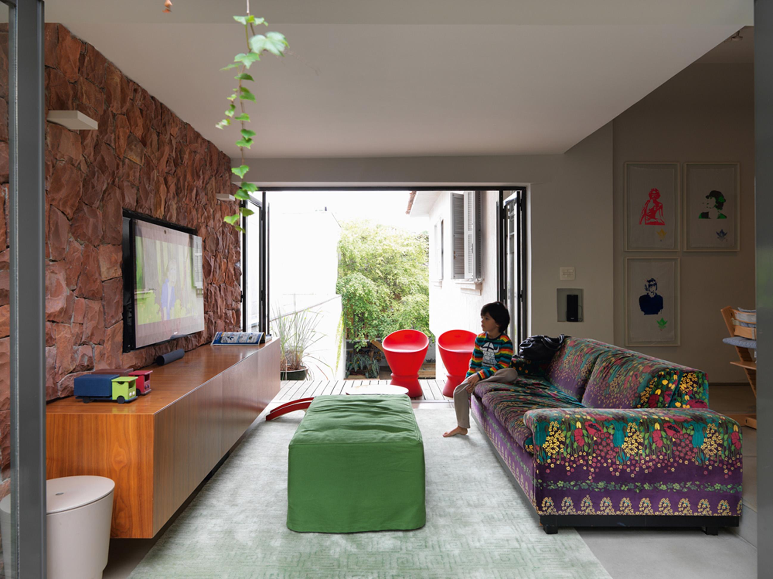 Parede sustentável: A sala tem parede com pedras originais da casa. O sofá com tecido de Adriana Barra é o preferido de Mathias, 5. Nas molduras de acrílico, panos de prato com figuras da moda, da Loja do Bispo