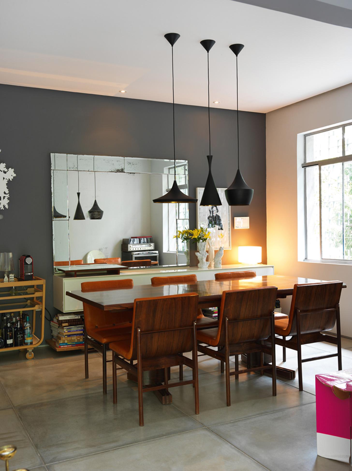 Reflexo natural: O espelho da sala de jantar é original da casa e sobreviveu à reforma. Carrinho de chá da Ikea. O aparador branco é da Micasa. A mesa e as cadeiras de jantar são de um antiquário, e os lustres, Tom Dixon