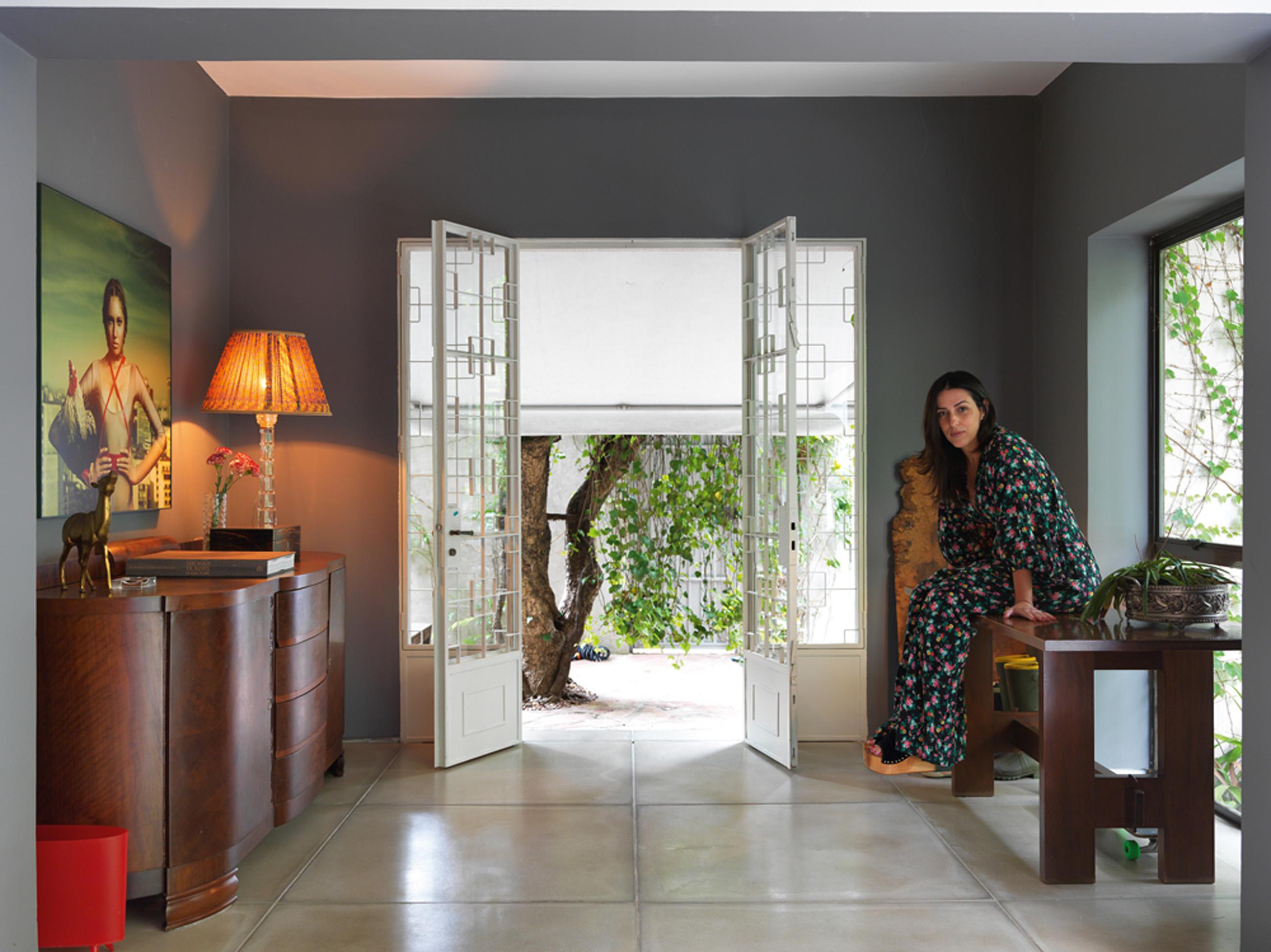 Vintage Real: A porta de entrada é original. O piso foi trocado por placas de concreto Solarium. O bufê da esquerda, presente da mãe, foi comprado em um antiquário. Abajur de Juliana Benfatti