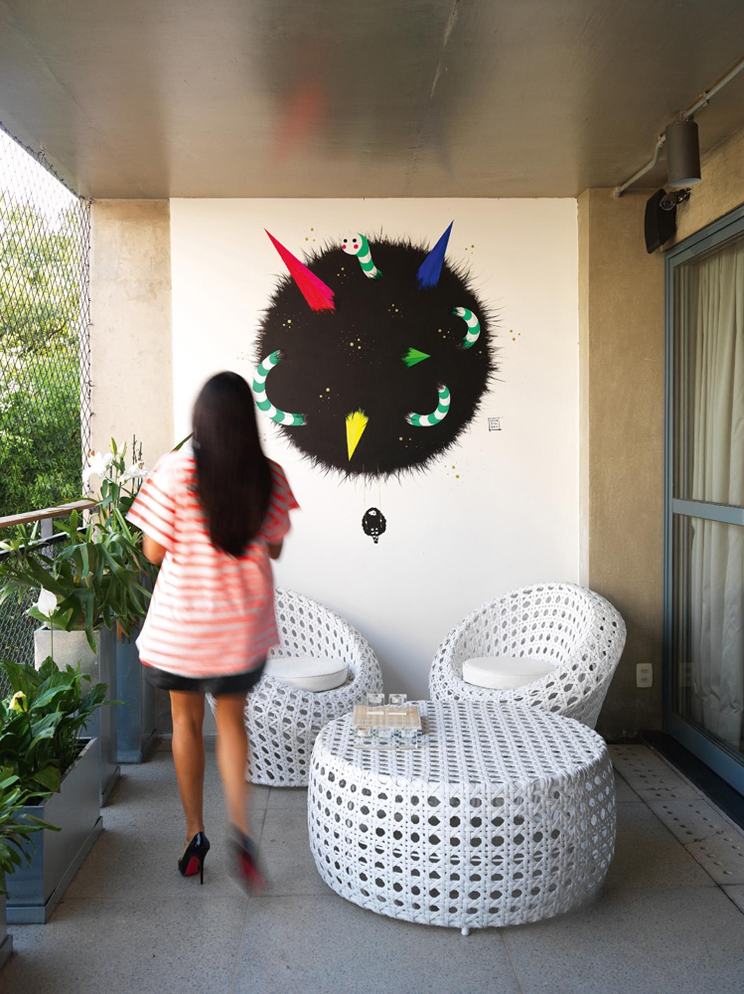 Parede pintada: A varanda tem móveis de fibra sintética da Okka Móveis e pintura na parede de Erica Mizutani