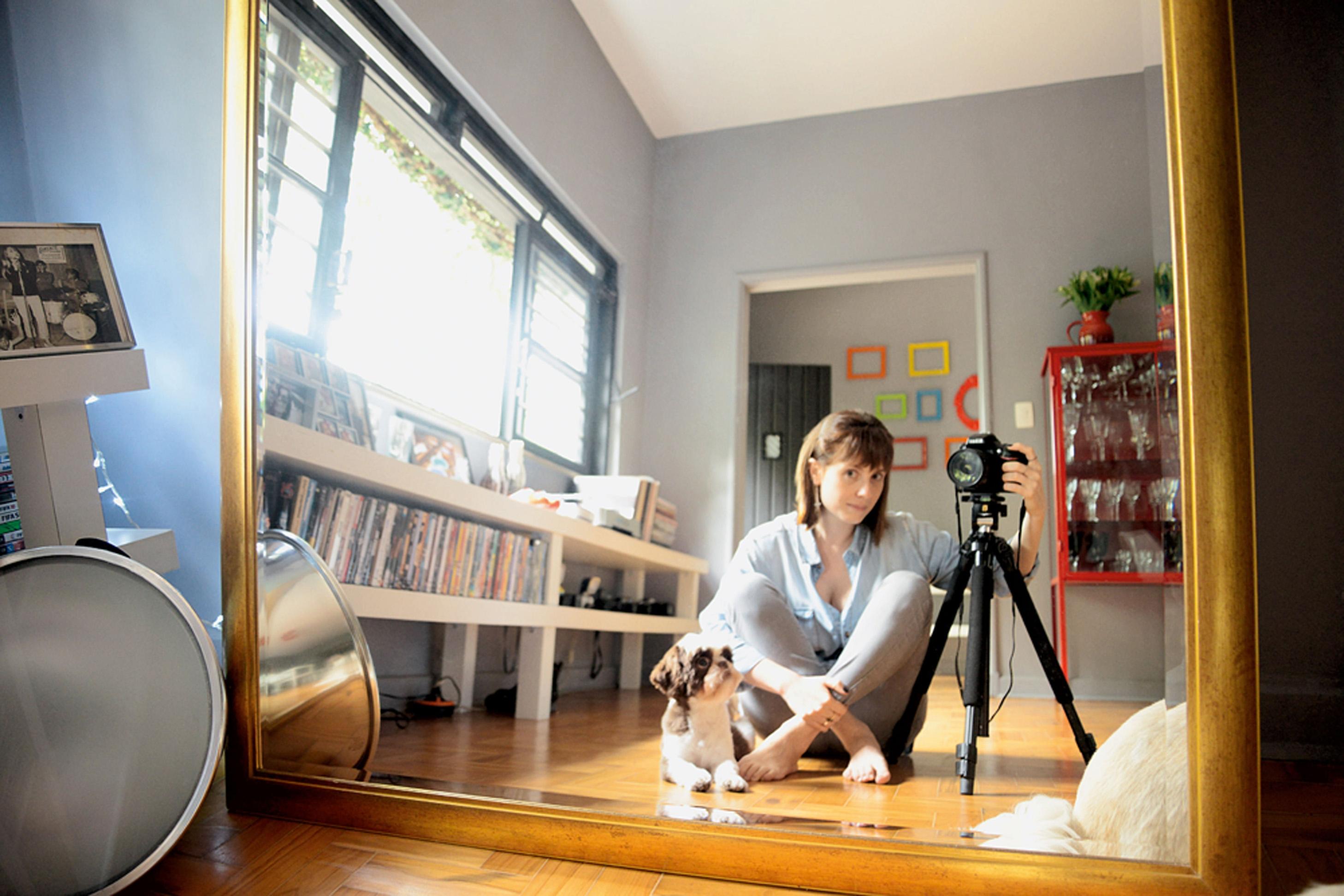 Autorretrato: Na sala de jantar, Mariana posa junto com a cadela Carlota em frente ao espelho gigante que mandou fazer