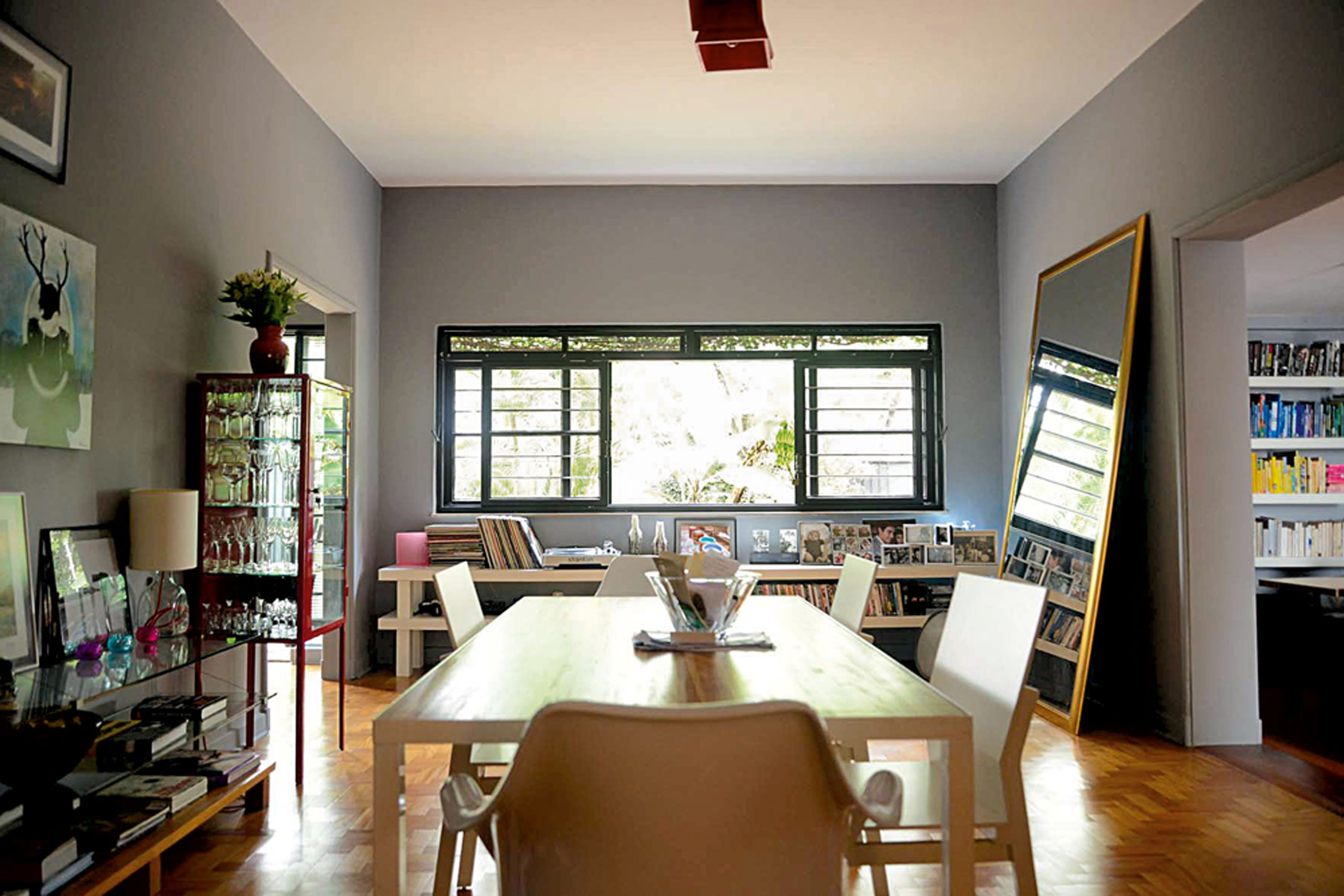 Multiuso: Nesta outra vista da sala de jantar, a cristaleira de metal vermelha foi feita em uma empresa que fabrica farmácias para pet-shops. Mesa de jantar e cadeiras da extinta loja Teto