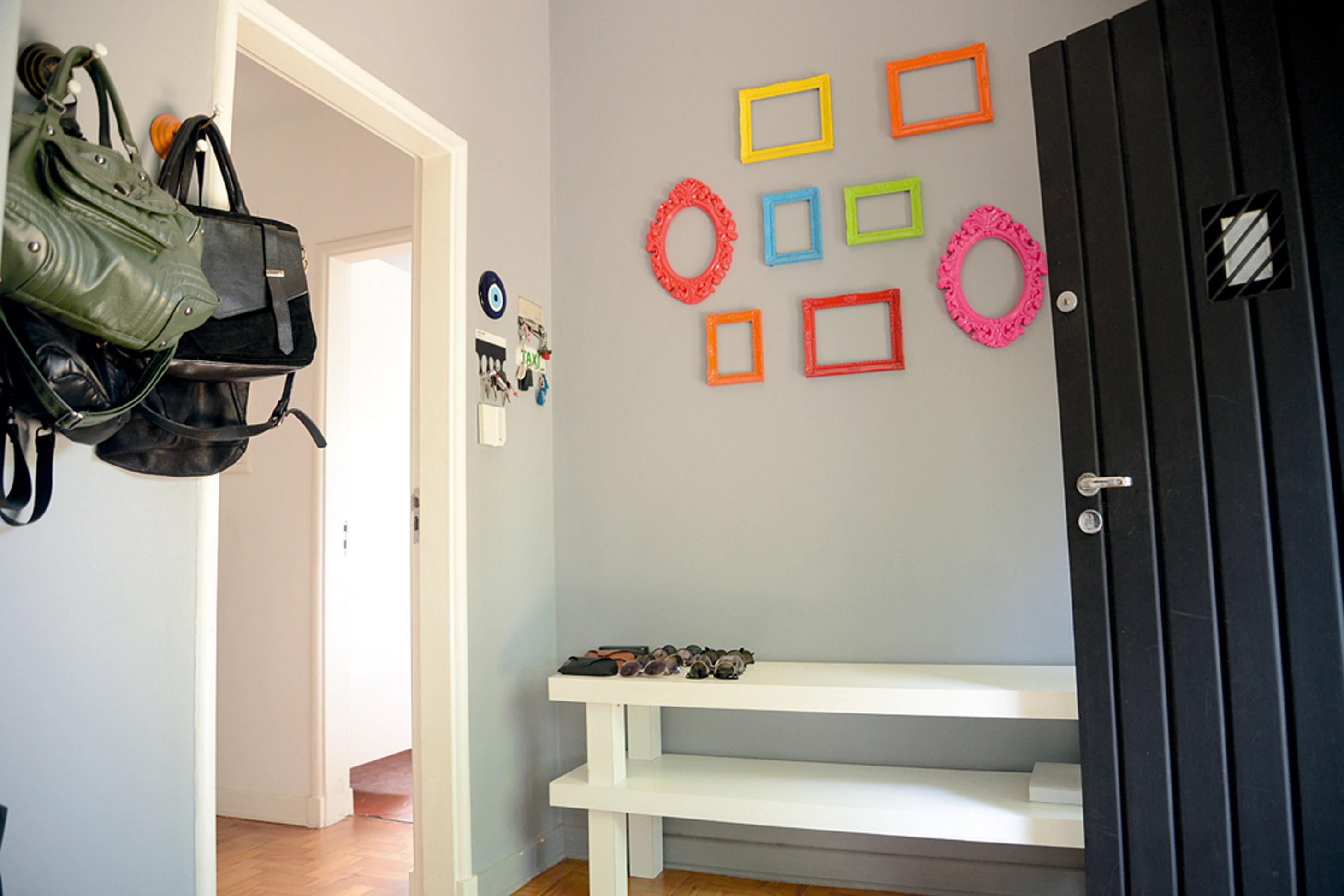 Bem-vindos: Molduras coloridas se destacam na parede cinza do hall de entrada. Um pedaço de estante do antigo apartamento serve como abrigo para bolsas, chaves, óculos e miudezas do dia a dia