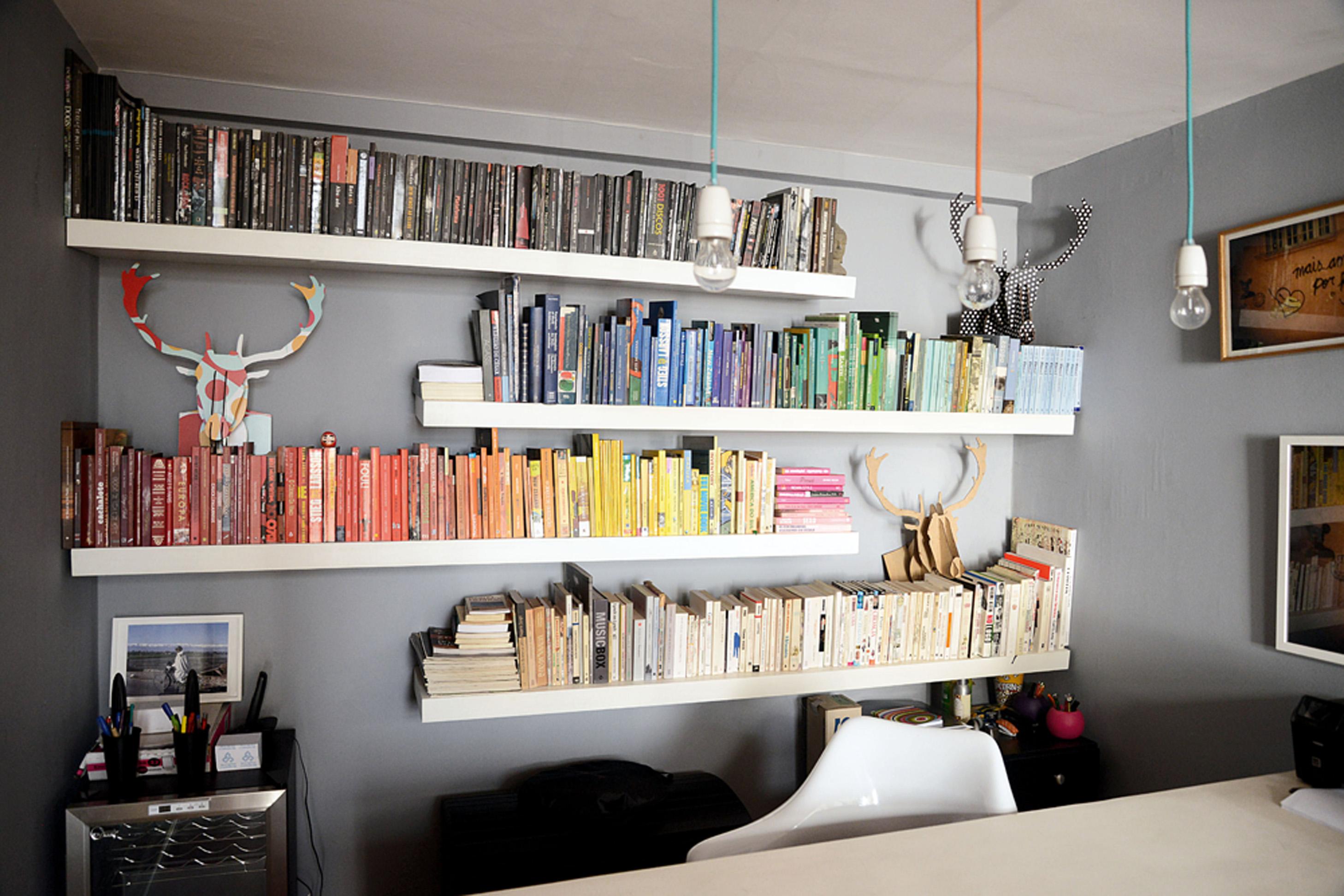 Rainbow: Mariana organizou os livros do escritório por cores, para que se destacassem ainda mais sobre a parede cinza