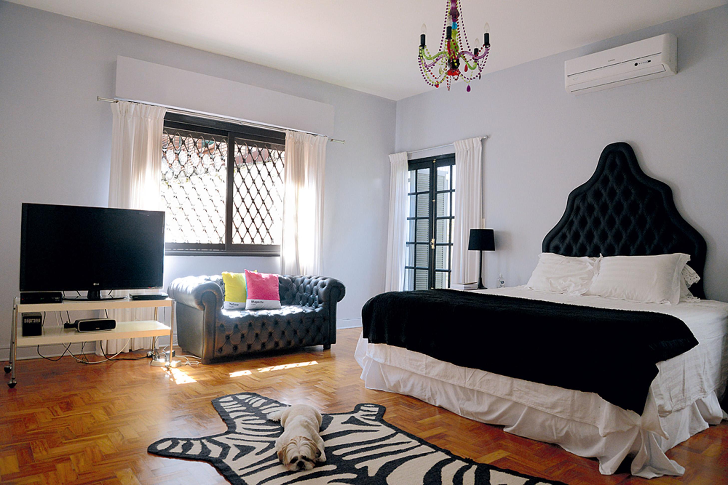 Refúgio: A cabeceira da cama foi comprada em uma feira de móveis usados. Sofá chesterfield, da Desmobilia, e Mirandinha, o outro pet da família, que descansa sobre o tapete Jonathan Adler