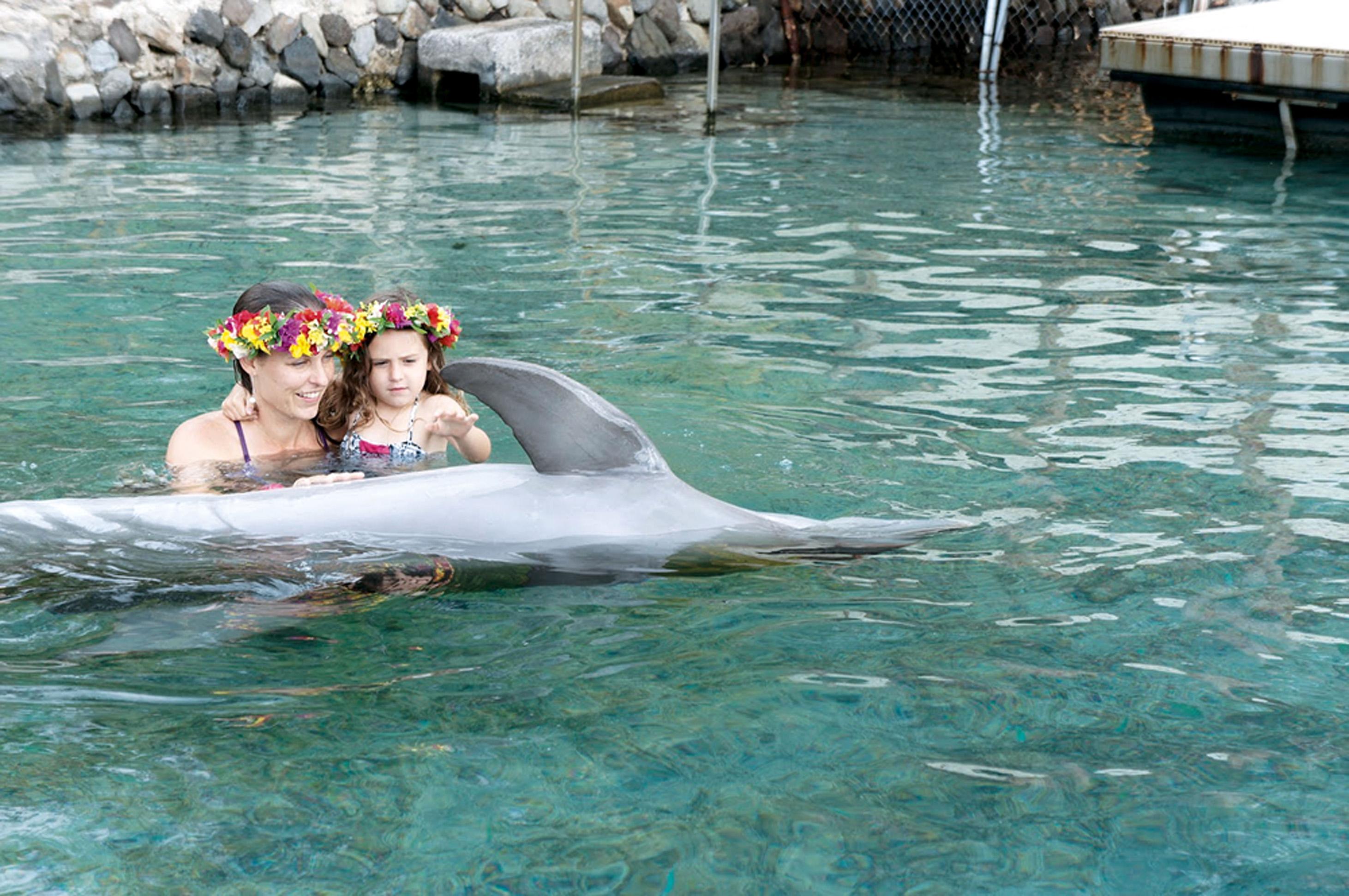 Mãe e filha com os golfinhos, no Taiti