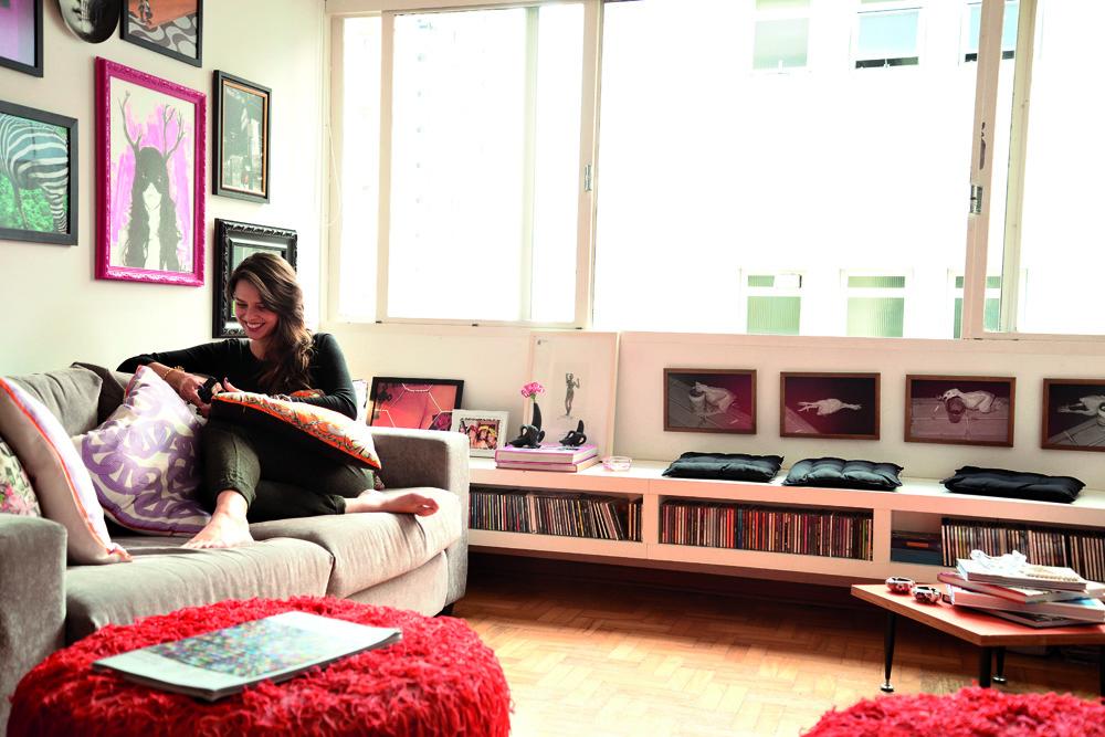 """À mão: Luciana só """"recheou"""" as paredes e personalizou os móveis. As almofadas do sofá fez com lenços de seda. O quadro pink é de Thiago Verdeee, da galeria Urban Arts. Acima do móvel branco, série de fotos feitas por ela com um frango de borracha. Almofadas de futon da Oppa. Vasinhos de banana de Jonathan Adler"""
