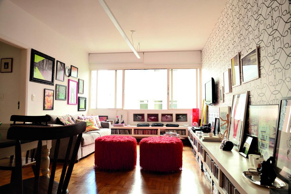 Herança: Visão geral da sala. Os pufes vermelhos foram feitos pela mãe de Luciana. O móvel branco serve de porta-CDs e bancada e percorre toda a sala