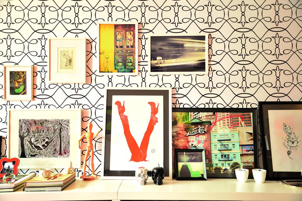 Exposição: Na sala, papel de parede Bobinex assinado por Marcelo Rosenbaum. A xilogravura e as outras ilustrações já estavam na casa. Velas em formato de caveira da John John e porta-velas da Oppa