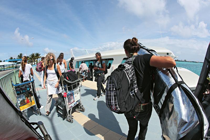Acima, mulherada reunida: do aeroporto para o barco de apoio