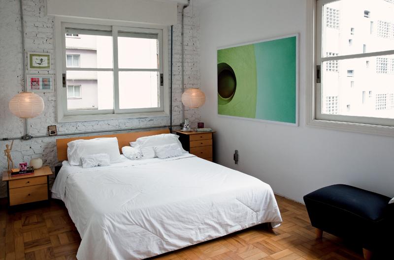 O quarto, amplo e com duas janelas, é xodó do casal. A parede deu trabalho para os pedreiros, que penaram para descascá-la e chegar aos tijolinhos aparentes. A foto, de Zé Gabriel Lindoso, retrata uma das janelas da Oca, em São Paulo