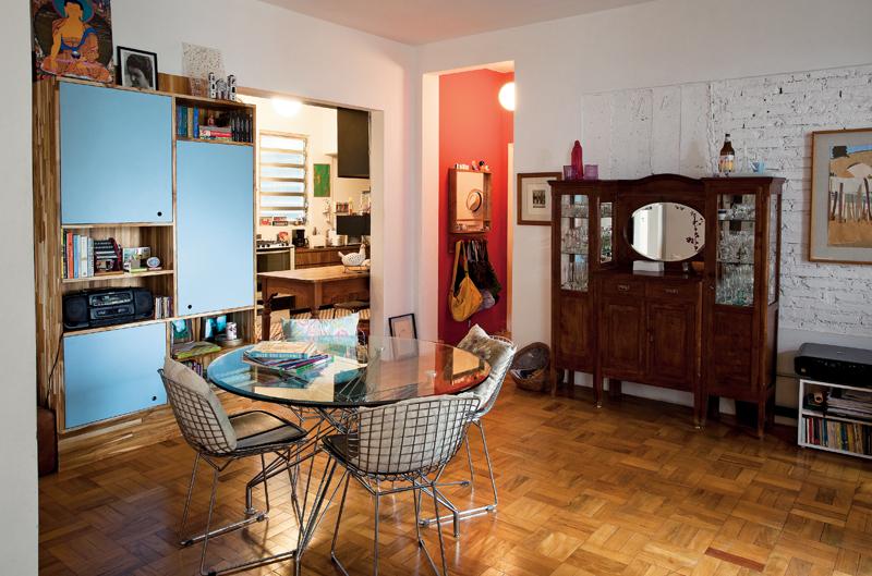 A estante de madeira e fórmica azul foi desenhada por Graziella e executada pela Madero Marcenaria. A mesa e as cadeiras são da Maria Jovem e a cristaleira antiga veio da casa da mãe de Leandro