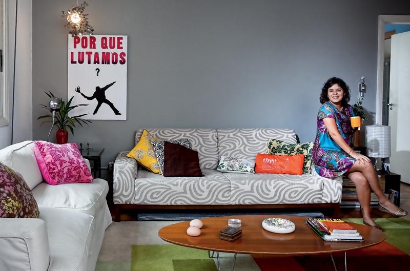 Sofá, tapete e mesa de centro de Fernando Jaeger. Almofadas Etnix – a laranja, de passarinho, é da designer Alice Abramo. A parede vai continuar cinza quando o espaço virar o quarto do Raul porque a cor é neutra e o casal adora. Pôster do coletivo Bi
