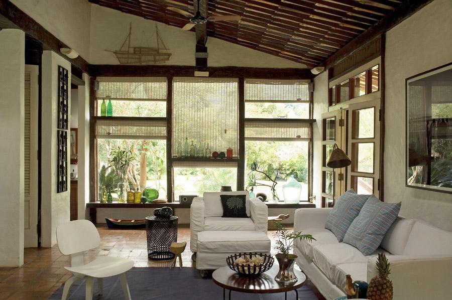 A poltrona antiga  foi comprada  em São Sebastião  Os sofás, brancos, têm duas capas – estão sempre limpos. As almofadas  têm tecido da Jacaré  do Brasil. Ninguém entra na casa de sapatos
