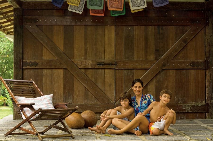 João, Regina  e Antônio em frente ao portão da garagem que abriga bote, pranchas e boias.  As bandeirinhas budistas de oração protegem a família