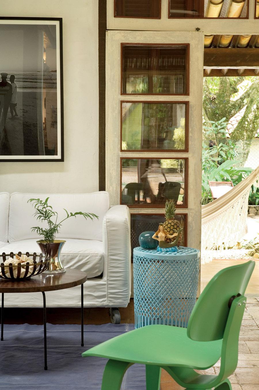 O sofá branco tem rodízios para que possa ser movimentado por toda a sala.  A mesinha de ferro azul é da Coisas  da Dóris e a cadeira verde, da Atrium