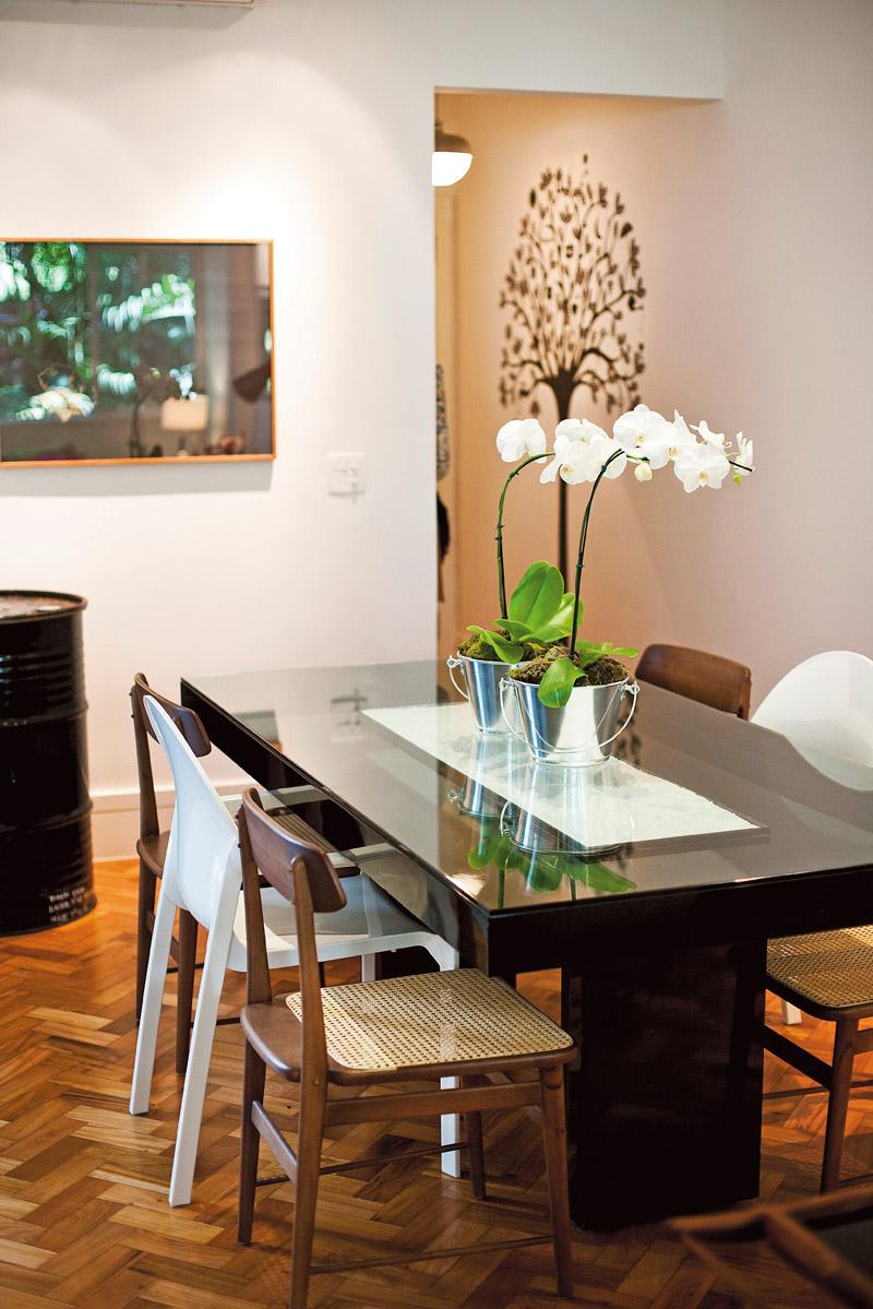 O adesivo de árvore, da Gecko, dá as boas-vindas aos convidados. Mesa de jantar pigmento, da ,Ovo. Mix de cadeiras, entre elas a Lucio, de Sergio Rodrigues, e a Tosca, de Richard Sapper