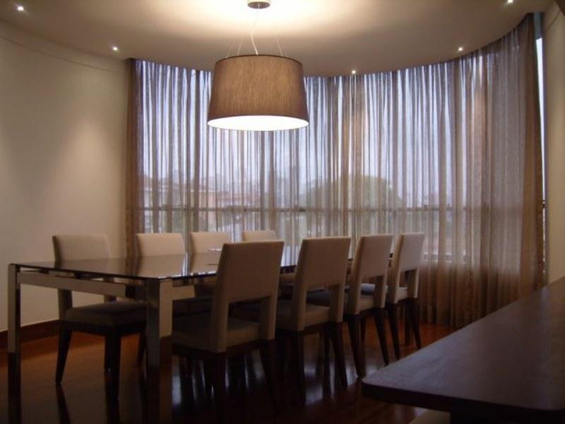 Cortina em gaze de Linho em trilho curvo embutido no cortineiro (Luxaflex por Duetto Decorações – www.duettodecoracoes.com.br)