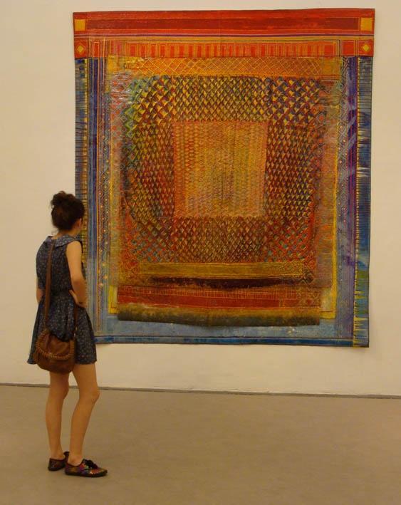 Uma visitante aprecia a obra de Delson Uchôa, no pavilhão do Brasil