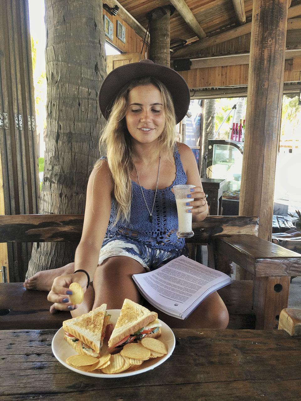"""10h40 """"Depois do treino, hora de se alimentar! Este café em frente à praia é de um inglês e uma chinesa. Tomei uma vitamina de banana e comi um sanduíche vegetariano."""""""