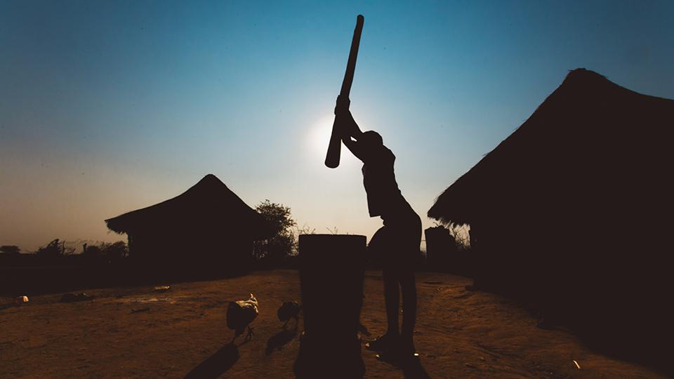 Criança pilando milho na vila de Mugurameno, Zâmbia. O povo Goba até hoje planta, seca, descasca e moe seu próprio milho