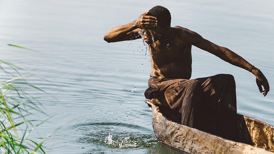 Jovem pescador se refresca no rio Zambeze. Na Zâmbia, as crianças aprendem a pescar desde cedo, dividindo seus dias com hipopótamos e crocodilos