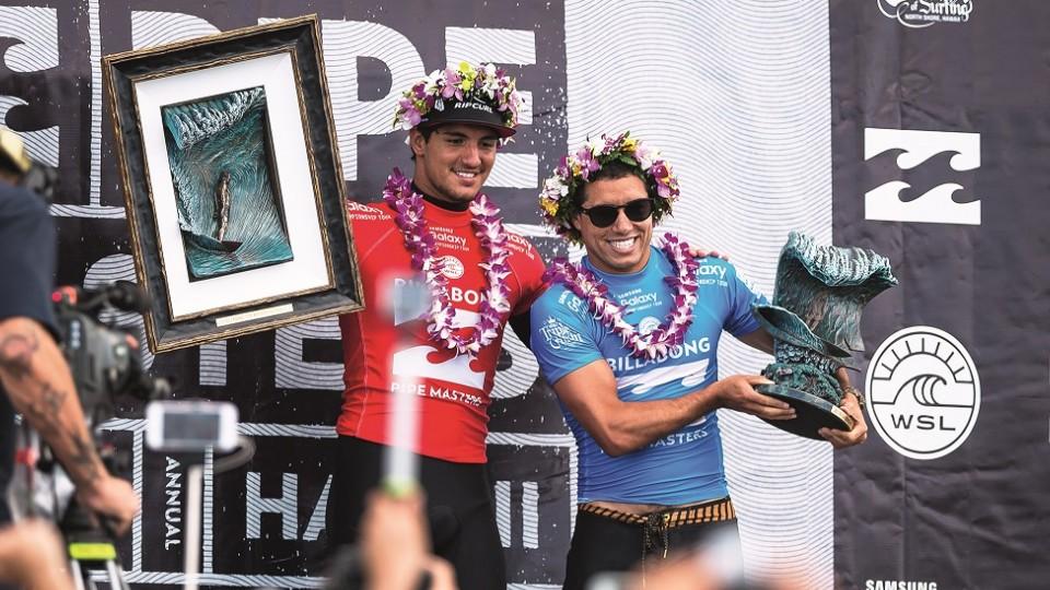 Adriano recebe o troféu das mãos do também campeão e amigo Gabriel Medina, em 2015, no Havaí