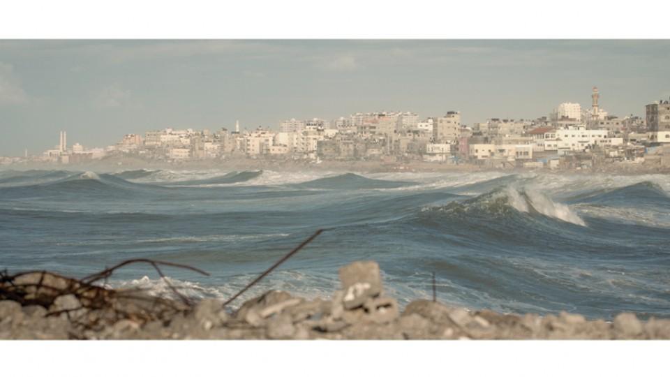Escombros da guerra emolduram as ondas em um cenário desolador