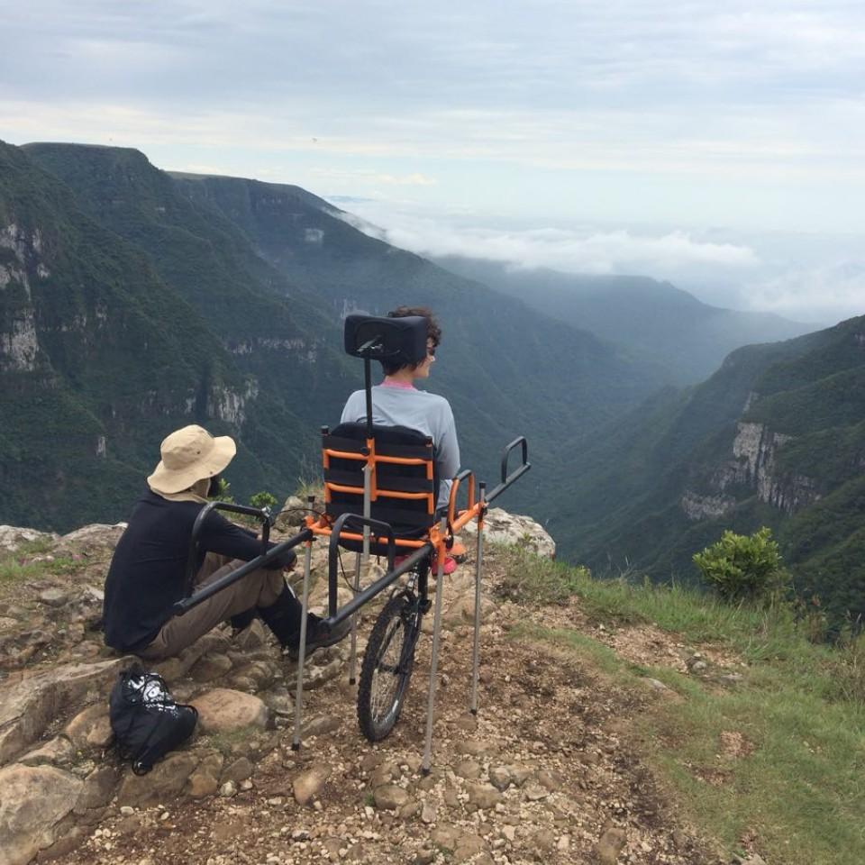 O casal Guilherme Simões e Juliana Tozzi, acompanhados da cadeira Julietti, invenção que eles pretendem espalhar pelo mundo, criando condições para que outras pessoas com mobilidade reduzida possam praticar o montanhismo