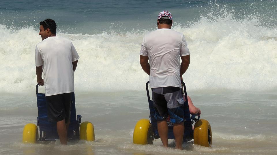 """""""A cadeira é só para a pessoa entrar no mar, depois, ela recebe ajuda de um instrutor. Para quem não anda é legal porque pode flutuar, alguns conseguem nadar, de forma bem livre"""", comenta Luiz Phelipe Nobre, da Adapt Surf"""