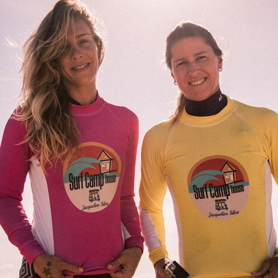 A repórter da Tpm Denise Aires veste o uniforme do Surf Camp de Jacqueline Silva (à dir.)