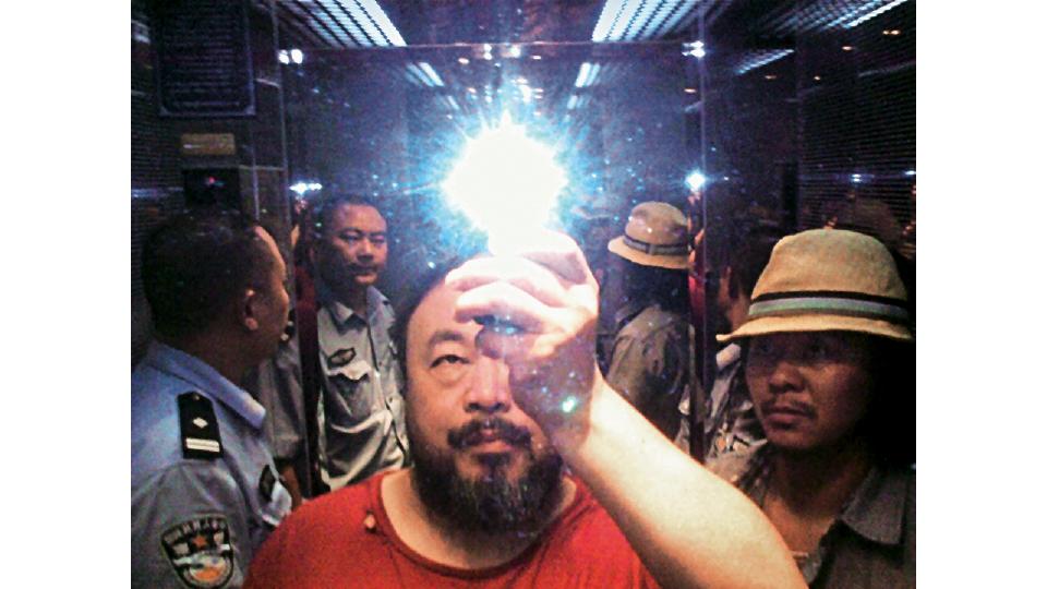 """Em 2009, Ai Weiwei pretendia testemunhar a favor de um ativista acusado de """"incitar a subversão"""" quando seu quarto foi invadido e ele, preso. Foi neste momento que ele tirou a selfie Illumination, enquanto era conduzido pelos policiais"""